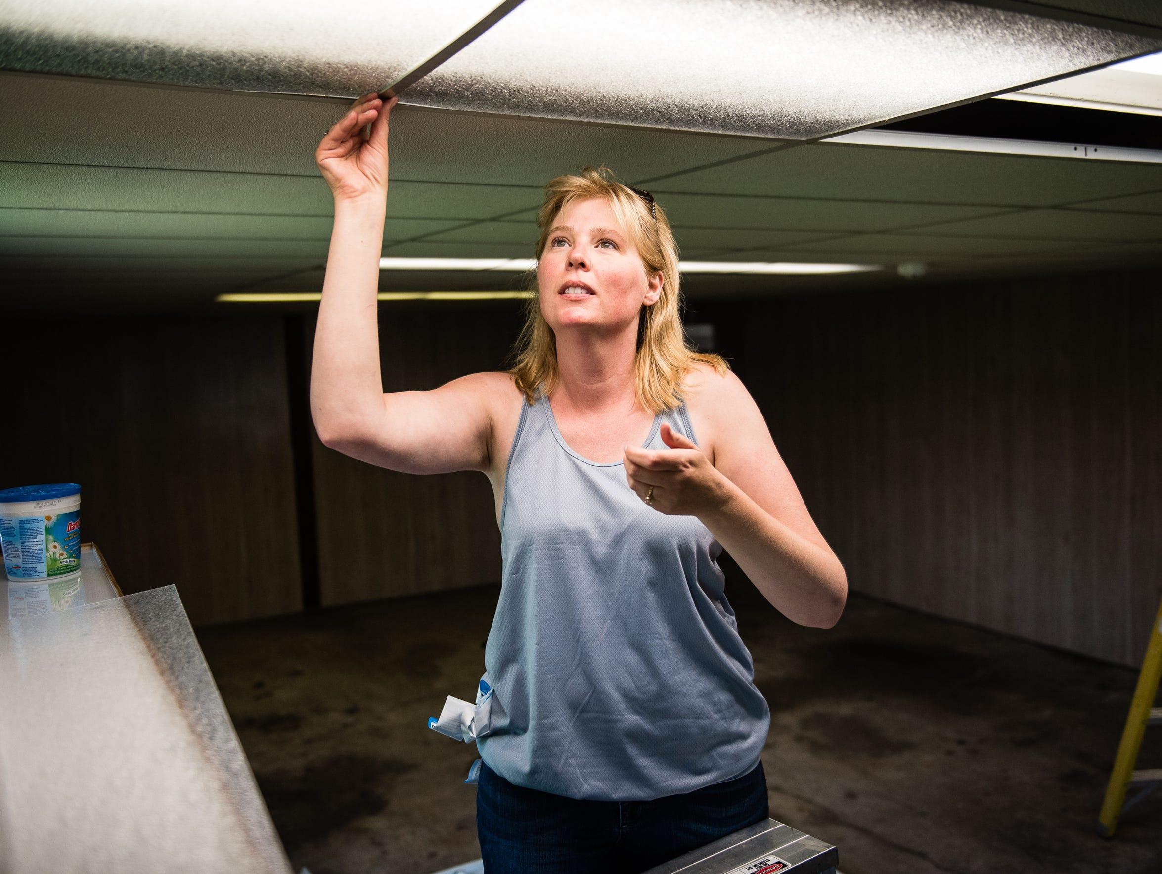Kirsten Schaub of Hanover works on ceiling light fixtures