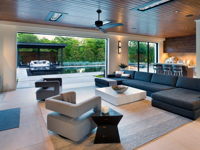 A Western Window multi-slide door on the heated terrace expands the outdoor living space in this contemporary modern home built by Castle Homes.