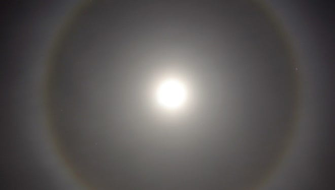 Tremblay captured the 13 day old moon with rings, a phenomenon created by the refraction of moonlight, really reflected sunlight, from ice crystals in the upper atmosphere. The shape of the ice crystals results in focusing the light into a ring. Because the ice crystals typically have a hexagonal shape, the Moon ring almost always is the same size of 22 degrees. Old folklore says that the number of stars within a moon halo indicate the number of days before bad weather will arrive, In this case, that's three..