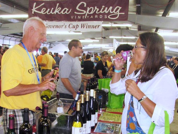 Jill Pavlot, of Clinton, N.Y., samples a glass of wine poured by T.J. Riley of Keuka Spring Vineyards on Sunday, June 13, during the Finger Lakes Wine Festival at Watkins Glen Racetrack.