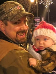 Thomas Zinkevich holds his 3-month-old son, Jase, for his first Hammonton Firemen's Christmas Parade.