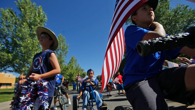 Members of the Bloomfield Bobcats baseball team ride their bikes on Monday in the city's annual Fourth of July parade.