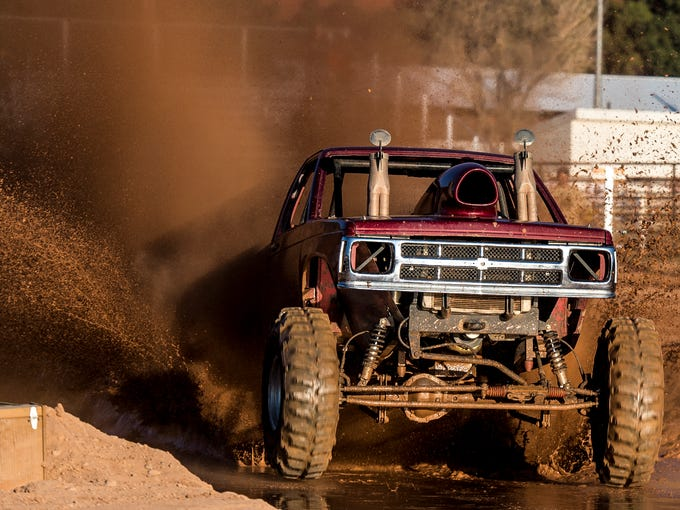 Trucks compete in a race through the mud in the Iron