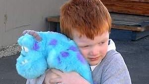 A four-year-old hugs a stuffed toy after escaping a mobile home fire in Stead this morning.