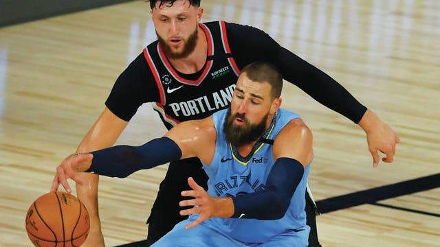 Memphis Grizzlies' Jonas Valanciunas, front, rolls around the Portland Trail Blazers' Jusuf Nurkic on Saturday.