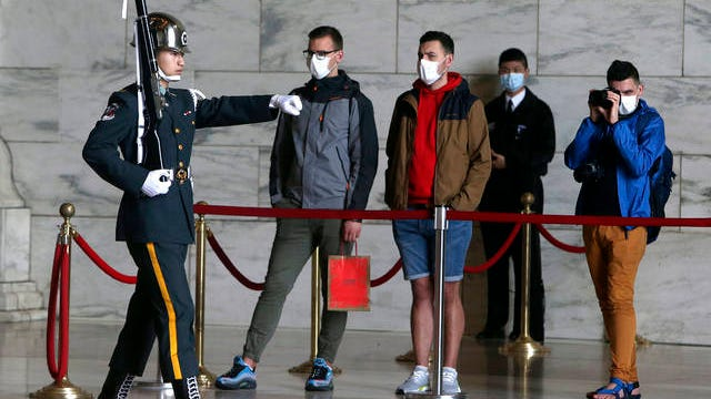 People wear face masks to protect against the spread of the new coronavirus at Chiang Kai-shek Memorial Hall in Taipei, Taiwan, Thursday. As the worst-hit areas of Asia continued to struggle with a viral epidemic, with hundreds more cases reported Thursday in South Korea and China, worries about infection and containment spread across the globe.