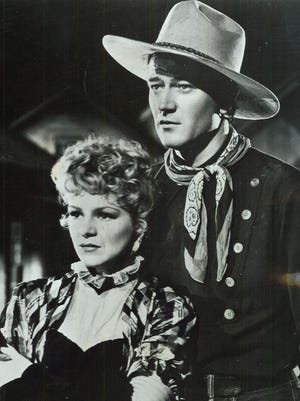 """John Wayne with Claire Trevor in the 1939 Oscar nominated film, """"Stagecoach."""""""