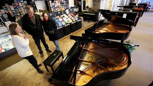Christi Foster Nunnally, left, shows a grand piano to customers Al and Jill Jorgensen in the Foster Family Music Center piano store showroom in Bettendorf, Iowa. The number of stores dedicated to selling pianos is dwindling across the country as fewer people take up the instrument and those who do opt for a used piano or a less expensive electronic keyboard.