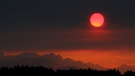 The sun turns red as it sets through the smoke behind the Olympic Mountains in Bremerton on Saturday, Aug. 22, 2015. The smoke from the Central Washington fires left a smoky haze over the area.