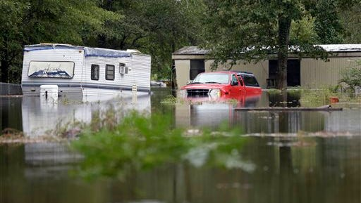 Water surrounds homes and cars in the Black Creek neighborhood following flooding in Florence, S.C., Monday.