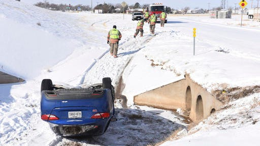 Randall County Emergency responders work an accident at Interstate 27 and Highway 2219, after a driver slide off the service road, in Amarillo, Texas, Friday, Jan. 6, 2017. One person was transported to nearby a nearby hospital. (Michael Schumacher/The Amarillo Globe News via AP)