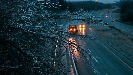 A Missouri Department of Transportation salt truck spreads ice melt on Interstate 55 as coated tree branches sway overhead as seen from the Main Street bridge on Friday, Jan. 13, 2017 in Festus, Mo.  A thick glaze of ice covered roads from Oklahoma to southern Illinois on Friday amid a winter storm that caused numerous wrecks, forced school cancellations, grounded flights and prompted dire warnings for people to stay home. (Robert Cohen/St. Louis Post-Dispatch via AP)