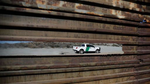 FILE - In this Nov. 9, 2016 file photo, a Border Patrol vehicle drives by in Tecate, Calif., seen through a hole in the metal barrier that lines the border in Tecate, Mexico. U.S. President Donald Trump will direct the Homeland Security Department to start building a wall at the Mexican border.