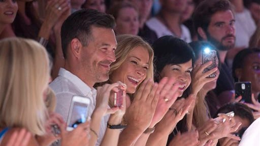 Country singer LeAnn Rimes, center, reacts after the Luli Fama collection during the Mercedes-Benz Fashion Week Swim show, Sunday in Miami Beach, Fla.