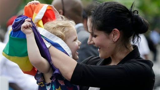 Ariel David, of New Orleans, who is gay, plays with a pride flag with her biological daughter Nelly David, 2, during a rally held in reaction to Sept. 3's decision by a federal judge, which upheld Louisiana's ban on same-sex marriages. A state judge on Monday ruled the ban is unconstitutional.