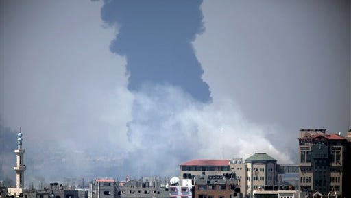 Smoke rises from an Israeli strike at a building in Gaza City, foreground, as black smoke billows from Gaza's electricity distribution company, background, after it was hit earlier by Israeli strikes in the Nusayrat refugee camp, central Gaza Strip, Tuesday, July 29, 2014.  Israel struck symbols of Hamas' control of Gaza and the strip's only power plant on Tuesday, escalating its military campaign against the Islamic militant group with the heaviest bombardment in the fighting so far.(AP Photo/Khalil Hamra)