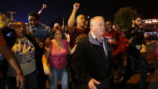 Ferguson Police Chief Tom Jackson begins to march with protesters before clashes led to arrests in front of the Ferguson Police Department, on Thursday, Sept. 25, 2014. (AP Photo/St. Louis Post-Dispatch, Robert Cohen)