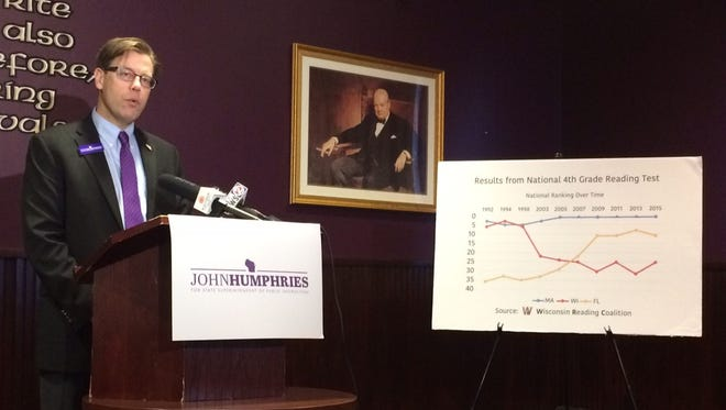 Standing next to a line graph from the Wisconsin Reading Coalition that shows how Wisconsin has fallen from third to 25th in state rankings for reading proficiency among fourth-graders, John Humphries of Mount Horeb announces a plan to repeal Wisconsin's Common Core testing standards during a news conference at St. Brendan's Inn in Green Bay on Thursday, Feb. 2, 2017. Humphries is a candidate for state superintendent of public instruction.
