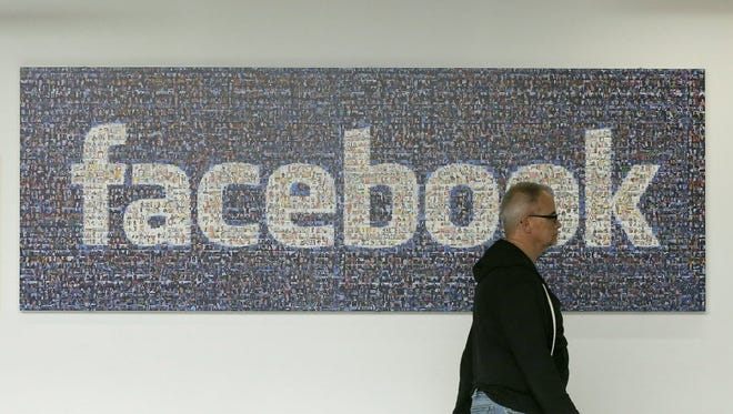 A man walks past a Facebook sign on the Facebook campus in Menlo Park, Calif.