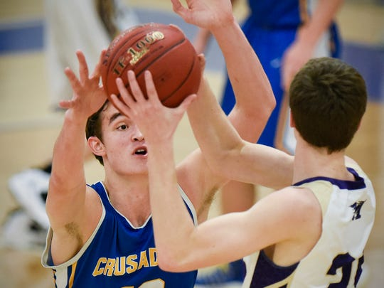 St. Cloud Cathedral's Mitchell Plombon, left, tries to block Melrose's Damon Van Beck from making a pass during the first half Tuesday, Jan. 17 at Cathedral High School.