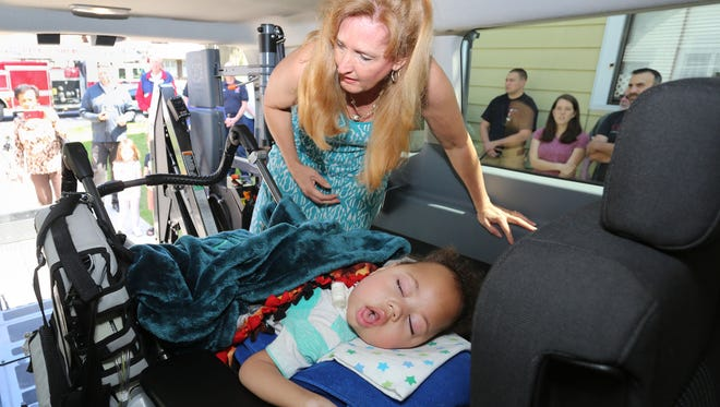 Cori Salchert secures a wheel chair to the new mobility gear on the family van with her son Charlie, 3, Thursday May 11, 2017 in Sheboygan, Wis. Make-A-Wish Foundation arranged to have mobility equipment installed in the Salchert 2016 Ford Van.