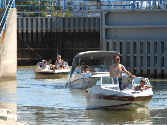 Boaters pass through the Fox River locks in De Pere.