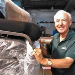 """Steve Hedlund unwraps one of the 180 brand new chairs patrons will enjoy for the first time this week during """"Damn Yankees"""" by the Iowa City Community Theatre."""