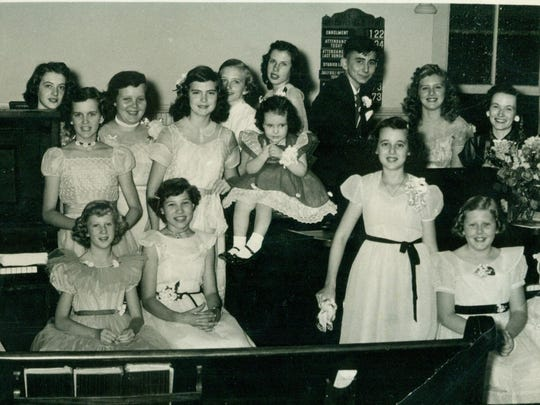 A piano recital at Malesus Baptist. Doris Clark, standing behind the flower arrangement on the piano, was the pastor's wife, and the youth pictured were her students. The church's current organist, Anne Bailey, is in the back row to the left of the enrollment board.