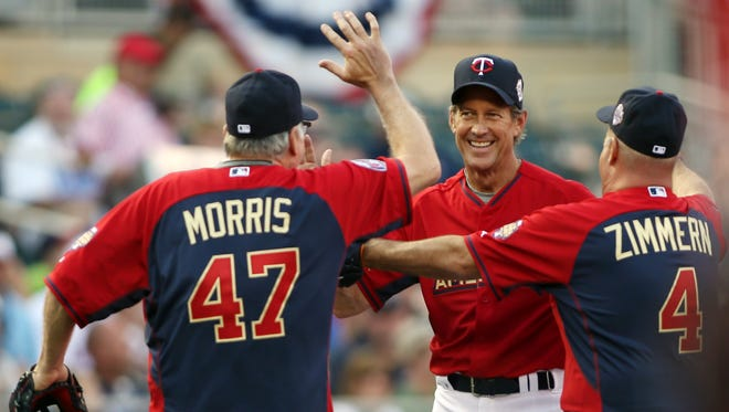 Television actor James Denton (middle) reacts with pitcher Jack Morris (left) and television personality Andrew Zimmern (4) after making a diving stop during the MLB legends and celebrity softball game at Target Field.
