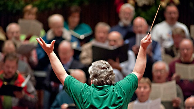 Daniel Spurlock, conductor of The Louisville Philharmonia, leading the orchestra with a choir during rehearsals for a past Christmas concert.