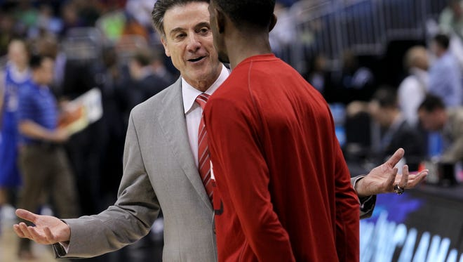 U of L head coach Rick Pitino instructs Russ Smith, #2, before the start of the second half against St. Louis during their NCAA Tourney game at the Amway Center in Orlando, Fl. Mar. 22, 2014
