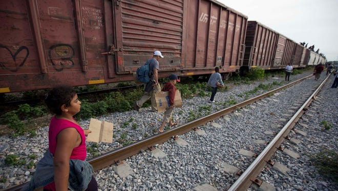 FILE - In this July 12, 2014 file photo, migrants walk along the rail tracks after getting off a train during their journey toward the U.S.-Mexico border in Ixtepec, Mexico. Many of the immigrants recently flooding the nation?s southern border say they?re fleeing violent gangs in Central America. These gangs were a byproduct of U.S. immigration and Cold War policies, specifically growing from the increase in deportations in the 1990s. With weak dysfunctional governments at home, U.S. street gang culture easily took hold and flourished in these countries. (AP Photo/Eduardo Verdugo)