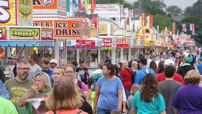 Visitors walk past food vendors at the Iowa State Fair on Aug. 7 in Des Moines, Iowa.