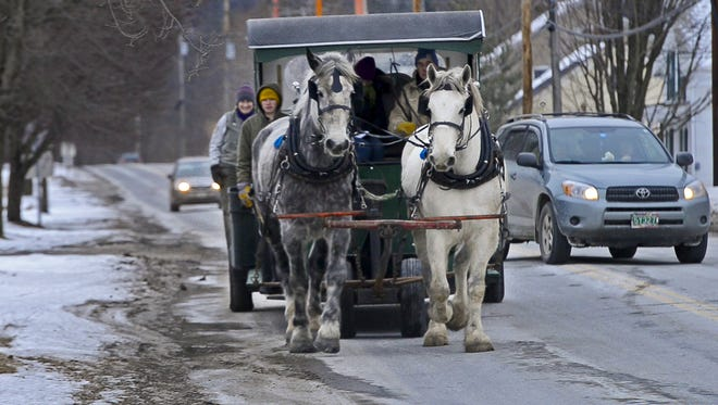 Patrick Palmer drives a team of Percheron horses to gather trash and recycling in Bristol, Vt., on Friday, Jan. 31, 2014.