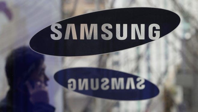 A man passes by the Samsung logo at its headquarters in Seoul, South Korea.