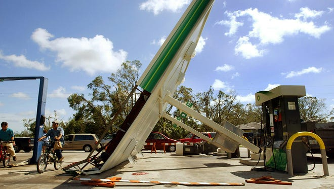 Bicyclists pass a toppled gas station roof August 15, 2004, in Arcadia, Fla., in Desoto County. At least 13 people were killed when Hurricane Charley left a path of destruction across Florida.