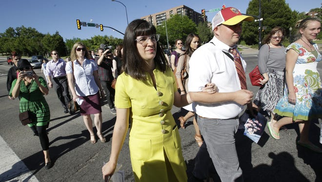 Kate Kelly, left, walks with supporters to the offices of the Church of Jesus Christ of Latter-day Saints on Sunday in Salt Lake City.