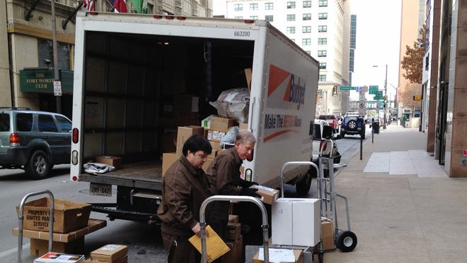 A three-man UPS crew unloads packages from a rented truck in Fort Worth, Texas, Friday, Dec. 27, 2013.