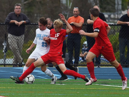 Ketcham's Josh Kowalsky, center, battles with John