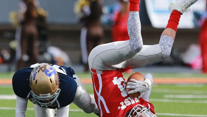 East receiver Jasper Escobedo lands upside down after being hit by the West's Marcos Aguilar after a reception during the first quarter Saturday. See more photos at elpasotimes.com.