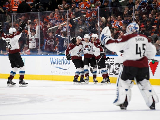 Colorado Avalanche's Nikita Zadorov (16), Tyson Barrie (4), J.T. Compher (37), Blake Comeau (14) and goaltender Jonathan Bernier (45) celebrate Compher's overtime goal against the Edmonton Oilers during an NHL hockey game Thursday, Feb. 1, 2018, in Edmonton, Alberta. (Codie McLachlan/The Canadian Press via AP)