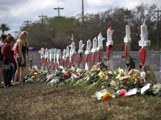 People visit a makeshift memorial setup in front of Marjory Stoneman Douglas High School on Feb. 19, 2018 in Parkland, Fla.  Credit: Joe Raedle, Getty Images