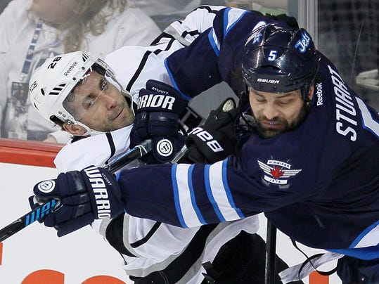 Winnipeg Jets' Mark Stuart (5) checks Los Angeles Kings' Jarret Stoll (28) during first-period NHL hockey game action in Winnipeg, Manitoba, Thursday, March 6, 2014. (AP Photo/The Canadian Press, John Woods)