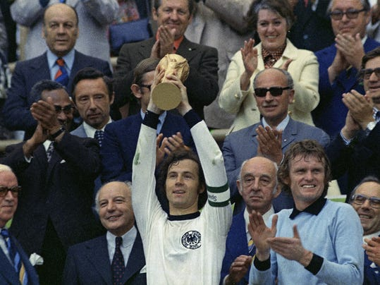 """FILE - In this July 7, 1974 file photo, West Germany captain, Franz Beckenbauer, holds up the World Cup trophy after his team defeated the Netherlands by 2-1, in the World Cup soccer final at Munich's Olympic stadium, in West Germany. Applauding at right, German goalkeeper Josef """"Sepp"""" Maier. On this day: West Germany wins its second World Cup after defeating the much-fancied Dutch. (AP Photo/File)"""