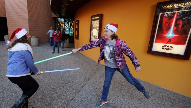 """Mak Tarr and Rose Cecrle duel with toy lightsabers while waiting in line to see """"Star Wars: The Last Jedi"""" Thursday at the Fort Worth Museum of Science and History's IMAX theater."""