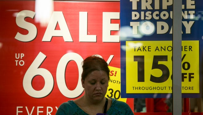 Veronica Gomez of Tolleson, Ariz., checks her phone while shopping Nov. 23, 2012, at Tanger Outlets at Westgate in Glendale, Ariz.