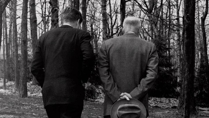 President John F. Kennedy, left, discusses the failed Bay of Pigs invasion with former president Dwight D. Eisenhower as they walk along a path at Camp David on April 22, 1961.