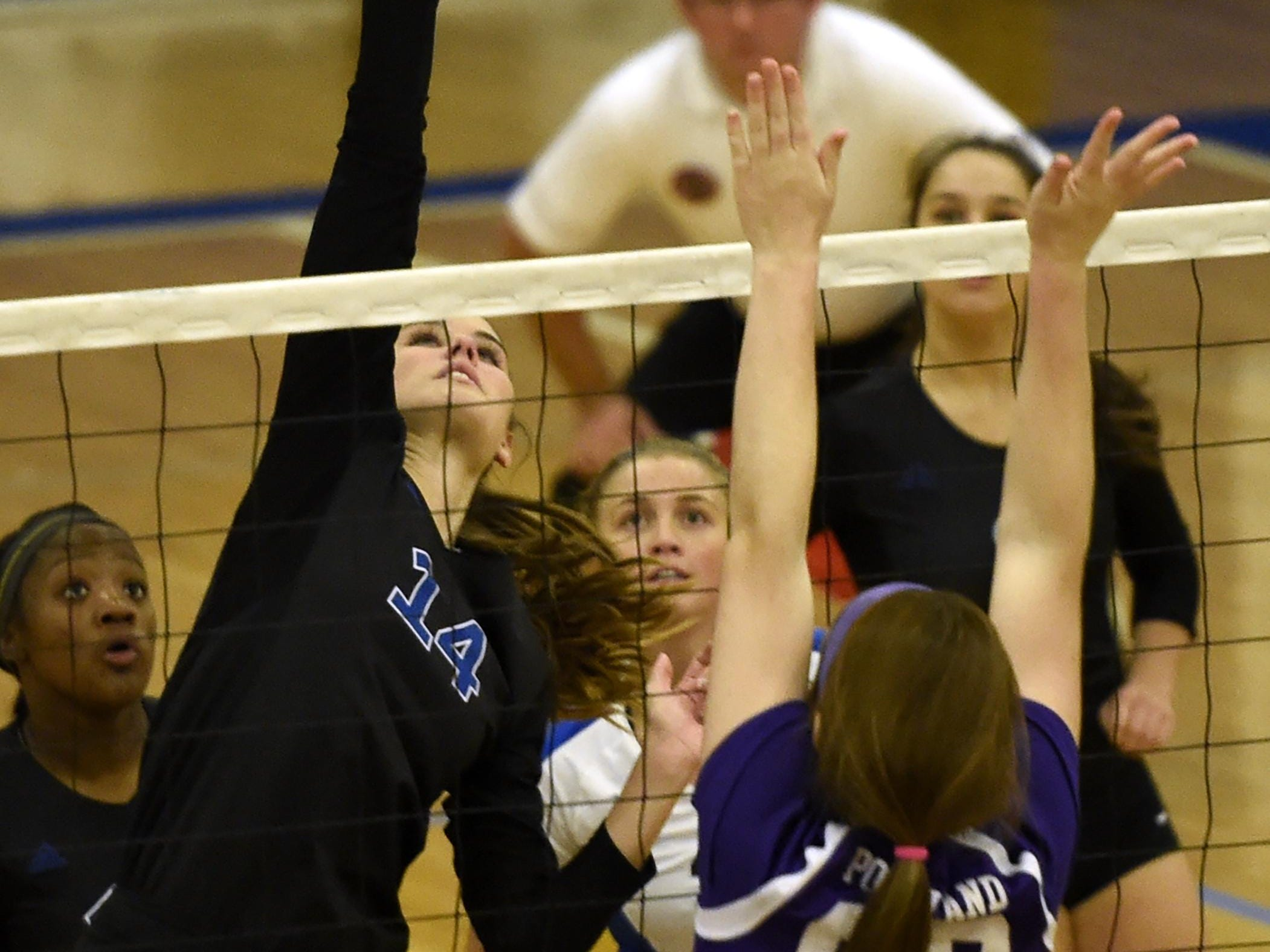 Brentwood's Kaela Massey (14) tips the ball over the head of Portland's Alexia Dorris (10) during their match in the Sub-State Volleyball tournament Thursday Oct. 15, 2015, in Brentwood, Tenn.