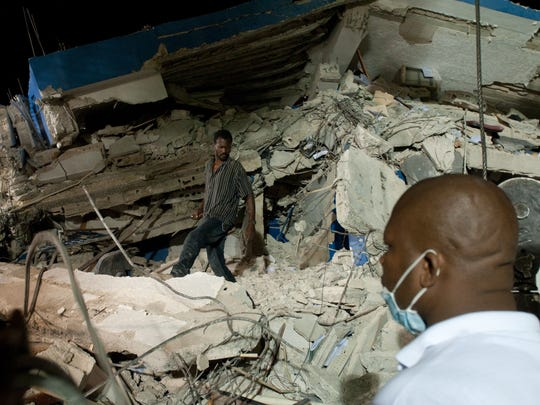 Jan. 12, 2010: 316,000 dead in Haiti. Rescue operators work through the night at a fallen police station in Port-au-Prince, Haiti, on Jan. 14, 2010.