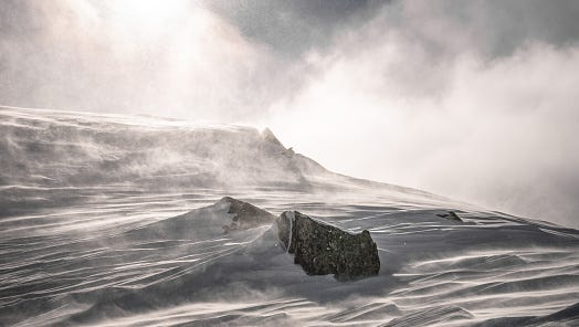 Storm forming on a snowy landscape.